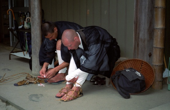 Two monks tying on their sandals for takuhatsu (ritual begging)