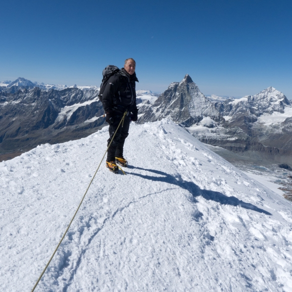 Me on the summit of Breithorn with the Matterhorn in the distance behind.