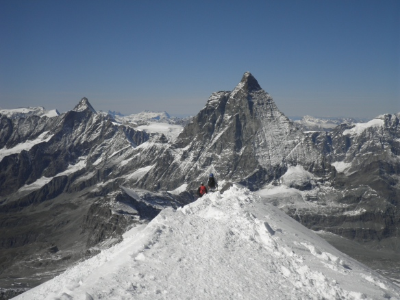 Summit ridge of Breithorn with the Matterhorn in the distance.